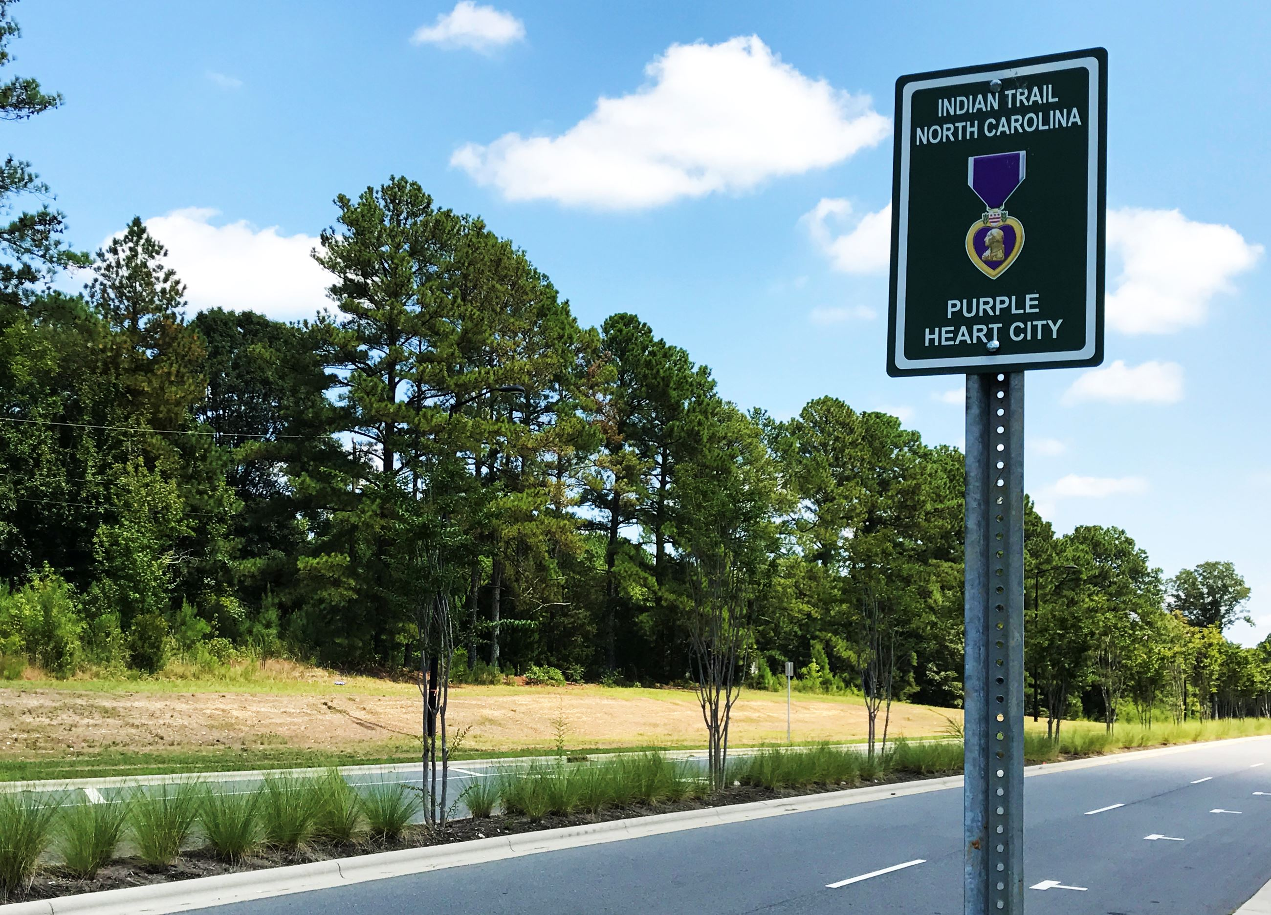 A Purple Heart City sign on Chestnut Parkway. Signs have been posted across Indian Trail marking the