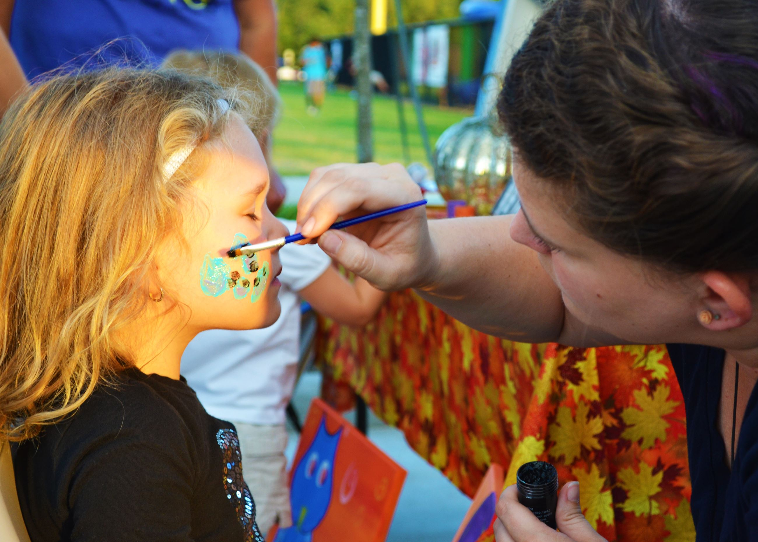 A girl gets her face painted before the movie