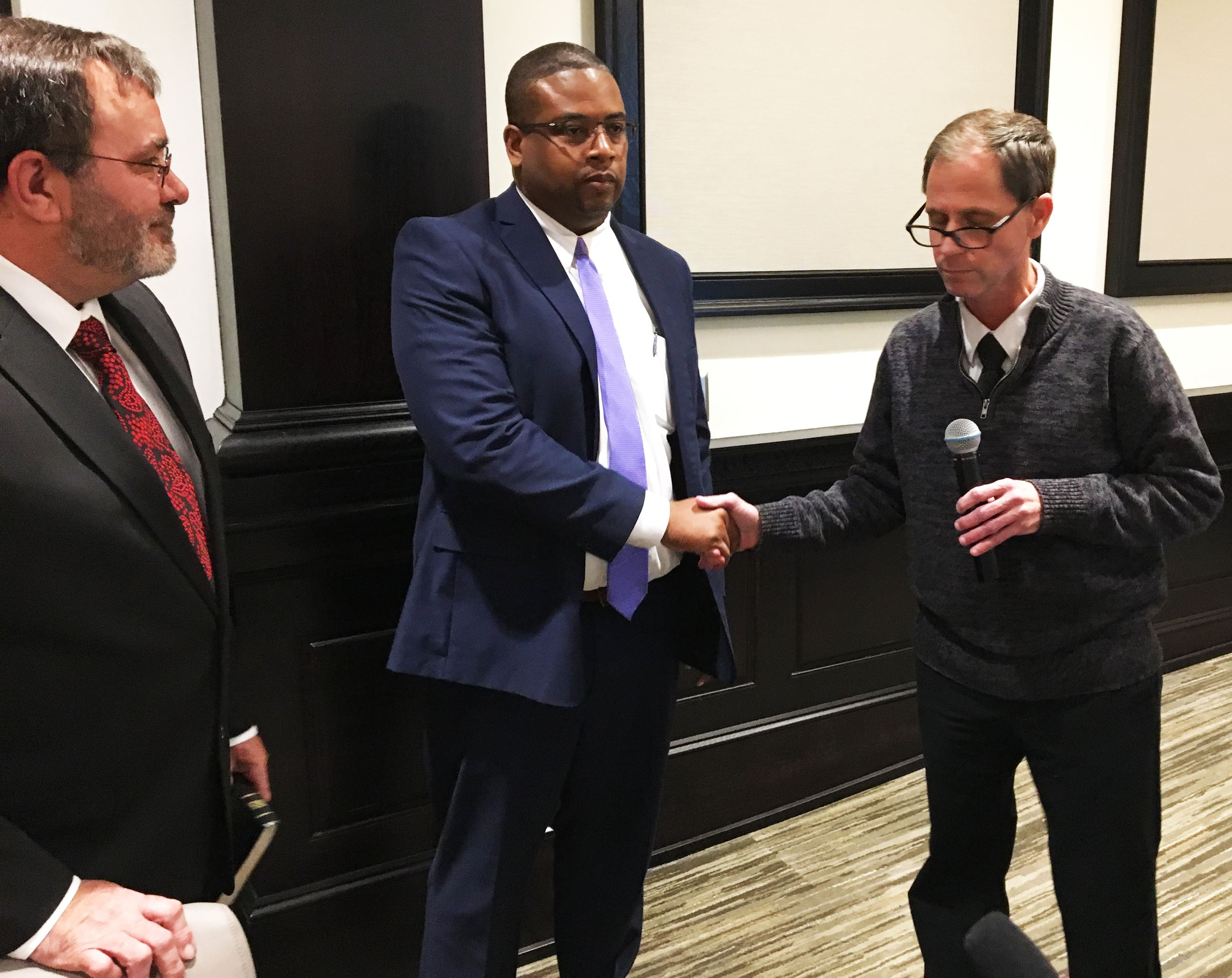 Marcus McIntyre (center) is sworn in with the help of Mayor Michael Alvarez (right) and Councilman J